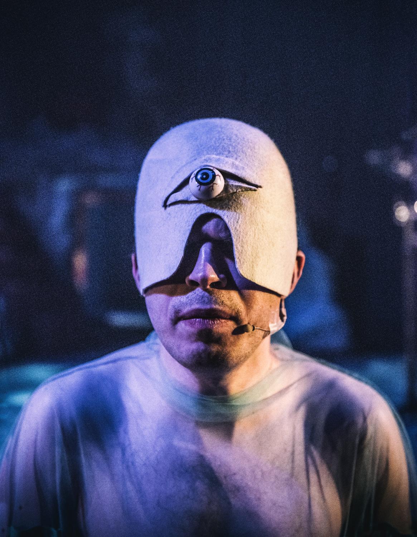 Aktor mający na sobie nakrycie głowy z jednym okiem na środku