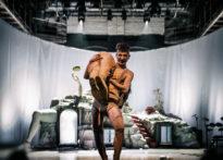 Aktor ubrany w cielisty strój niosący na rękach kobietę, w tle scenografia