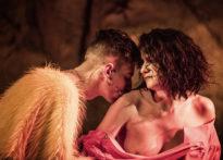 Aktor całujący w ramię na wpół gołą kobietę