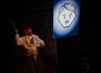 Aktor w stroju epokowym i przyczepionym wąsem trzymającym w ręku trzepaczkę. W tle obraz z podobizną Hitlera