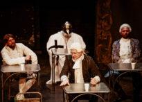 Czterech mężczyzn siedzących przy stołach. Trzej mają na sobie epokowe stroje i peruki, na samym końcu mężczyzna w zbroi rycerskiej.