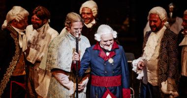 Siedmiu mężczyzn stojących na scenie w strojach epokowych i śmiejących się