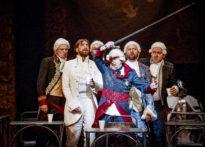 Sześciu mężczyzn stojących w grupie na scenie w strojach epokowych i perukach na tle arrasów