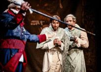 Dwóch mężczyzn ubranych w stroje epokowe i perukach, jeden trzyma w ręku but drugi kupek. Przed nimi mężczyzna w epokowym stroju z laską w ręce.
