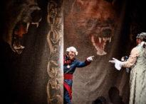 Dwóch aktorów stojących wśród arrasów w strojach epokowych