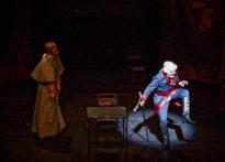 Aktor w epokowym stroju tańczący w świetle na scenie, za nim w mroku drugi mężczyzna w stroju epokowym.