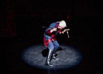 Aktor w świetle reflektora, ubrany w perukę oraz epokowy strój, który udaje, że gra na instrumencie w rzeczywistości grając na lasce