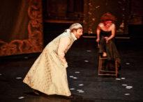 Aktor ubrany w strój epokowy idący przez scene, za nim kobieta stojąca na krześle w czarnej sukni