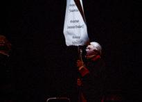 Aktor w stroju epokowym i peruce niosący transparent