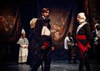 Aktorzy w perukach i strojach epokowych chodzący po scenie - zdjęcie zbiorcze