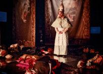 Aktorzy leżący na scenie, na środku mężczyzna ubrany w strój epokowy i duze nakrycie głowy z krzyżem na górze. W tle arrasy- zdjęcie zbiorcze