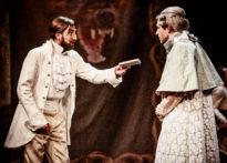 Dwóch mężczyzn w strojach epokowych i perukach, gdzie jeden daje drugiemu książkę. W tle arrasy