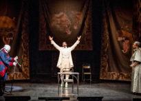 Stojący na środku sceny, mężczyzna ubrany w strój epokowy z rękoma uniesionymi do góry. Po jego prawej i lewej stronie dwóch mężczyzn w strojach epokowych i perukach. W tle arrasy