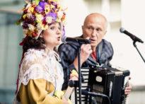 Aktorka w czapce z kwiatami na głowie śpiewająca do mikrofonu i aktor grający na akordeonie