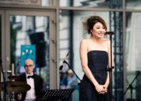 Aktorka ubrana w czarny strój śpiewająca do mikrofonu, w tle muzyk grający na perkusji