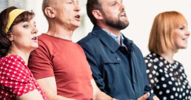 Aktorzy stojący na scenie i śpiewający do mikrofonu