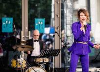 Aktorka ubrana w fioletowy strój śpiewająca do mikrofonu, w tle muzyk grający na perkusji