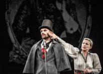 Mężczyzna stojacy na scenie przy mikrofonie mający na głowie cylinder, obok niego dotykająca jego twarzy kobieta