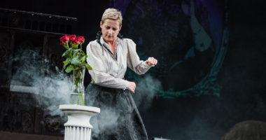 Aktorka stojąca koło wazonu z czerwonymi różami, w tle elementy scenografii i zdjęcie Marii Konopnickiej