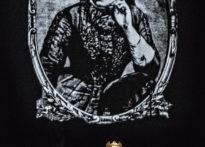 Aktorka siedząca na krześle z koroną na głowie, w tle czarno białe zdjęcie Marii Konopnickiej