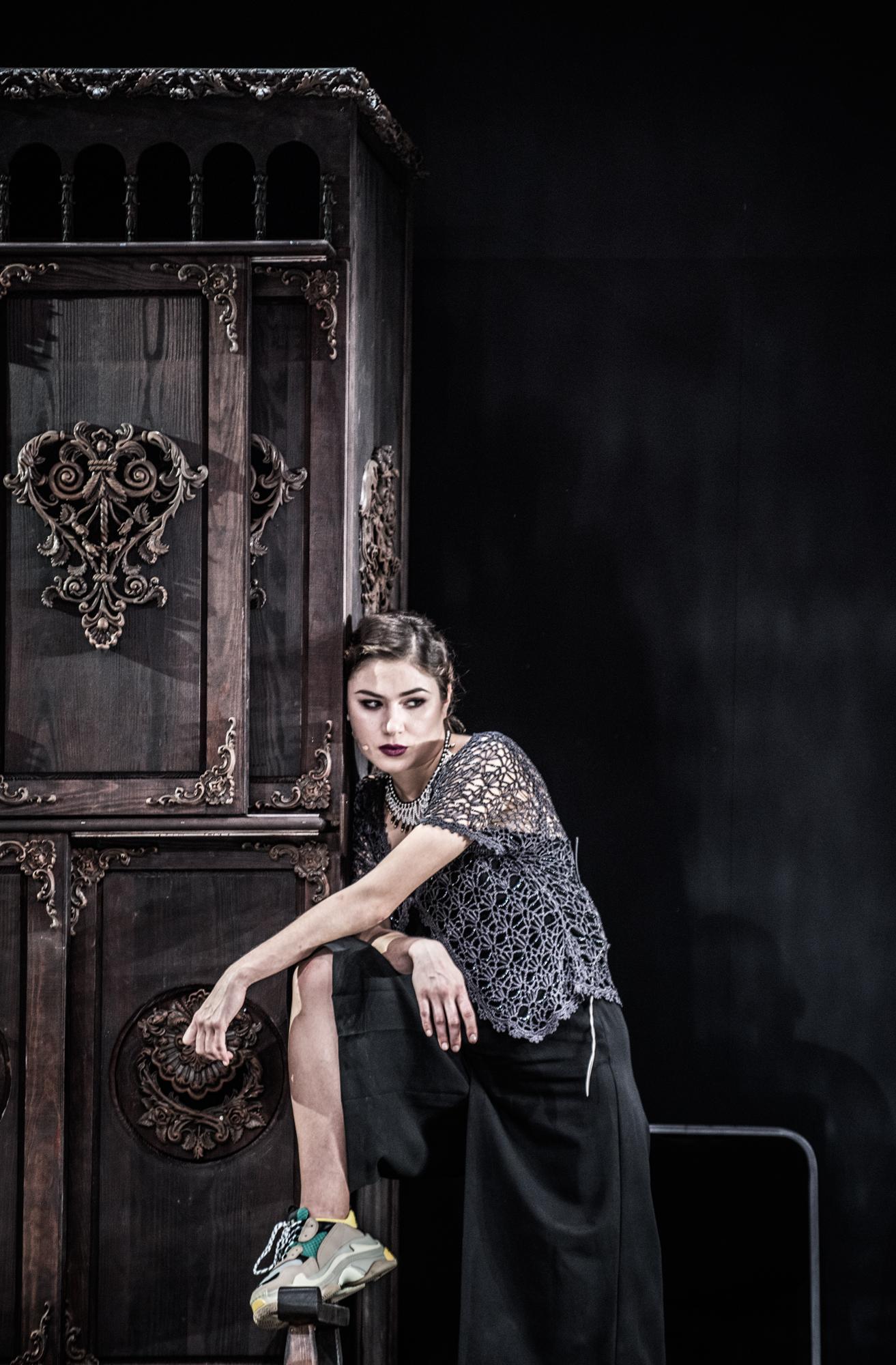 Aktorka stojąca na scenie przy dużej szafie z noga wspartą o element szafy