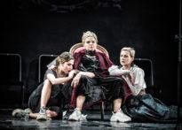 Aktorka w koronie siedząca na tronie, obok niej dwie siedzące na ziemi kobiety