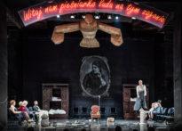 Aktorzy na scenie w różnych pozach, na pierwszym planie wiszący nad sceną słomiany wielki ptak