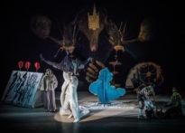 Dwóch aktorów na ciemnym tle tańczących na środku sceny w blasku reflektora, z góry pada na nich sztucznych śnieg. Z boku aktora w geście zwycięstwa. Na zdjęciu od lewej Elżbieta Węgrzyn, Kornelia Trawkowska oraz Wiesław Zanowicz.