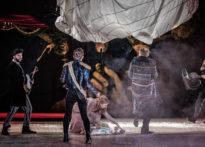 Pięciu aktorów stojących na scenie w różnych pozach oraz postać ubrana na czarno z dużą dmuchawą w ręce. Na zdjęciu od lewej Jakub Papuga, Konrad Cichoń, Kornelia Trawkowska, Wiesław Zanowicz, Piotr Kaźmierczak oraz Ryszard Zajączkowski