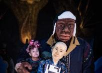 Aktorka na ciemnym tle w towarzystwie dwóch kukieł. Na zdjęciu Barbara Krasińska.