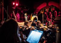 Na drugim planie zdjęcia w tle rozmazani aktorzy , na pierwszym planie kobiety- członkinie orkiestry grające na skrzypcach.