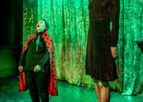 Aktora w przebraniu biedroneczki niskiego wzrostu oraz bardzo wysoki aktor ubrany w sukienkę , czerwone szpilki oraz czarną perukę na tle brokatowej kotary. Na zdjęciu Elżbieta Węgrzyn oraz Mateusz Wiśniewski