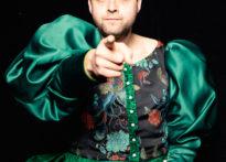 Portret mężczyzny ubranego w damską suknie wskazującego coś palcem