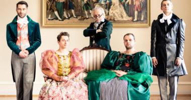 """Dwaj mężczyźni siedzący w damskich sukniach na zabytkowej sofie, obok nich oraz za nimi, ubrani w epokowe stroje trzej mężczyźni, Nad ich głowami wisi obraz - """"Książę Potocki ze swoja świtą"""""""