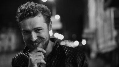 Czarno-biała fotografia uśmiechniętej twarzy głównego bohatera Hamleta, gościnnego aktora Romana Łuckiego