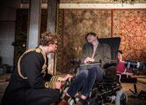Aktor ubrany w mundur kucający koło wózka inwalidzkiego na którym siedzi kolejny aktor