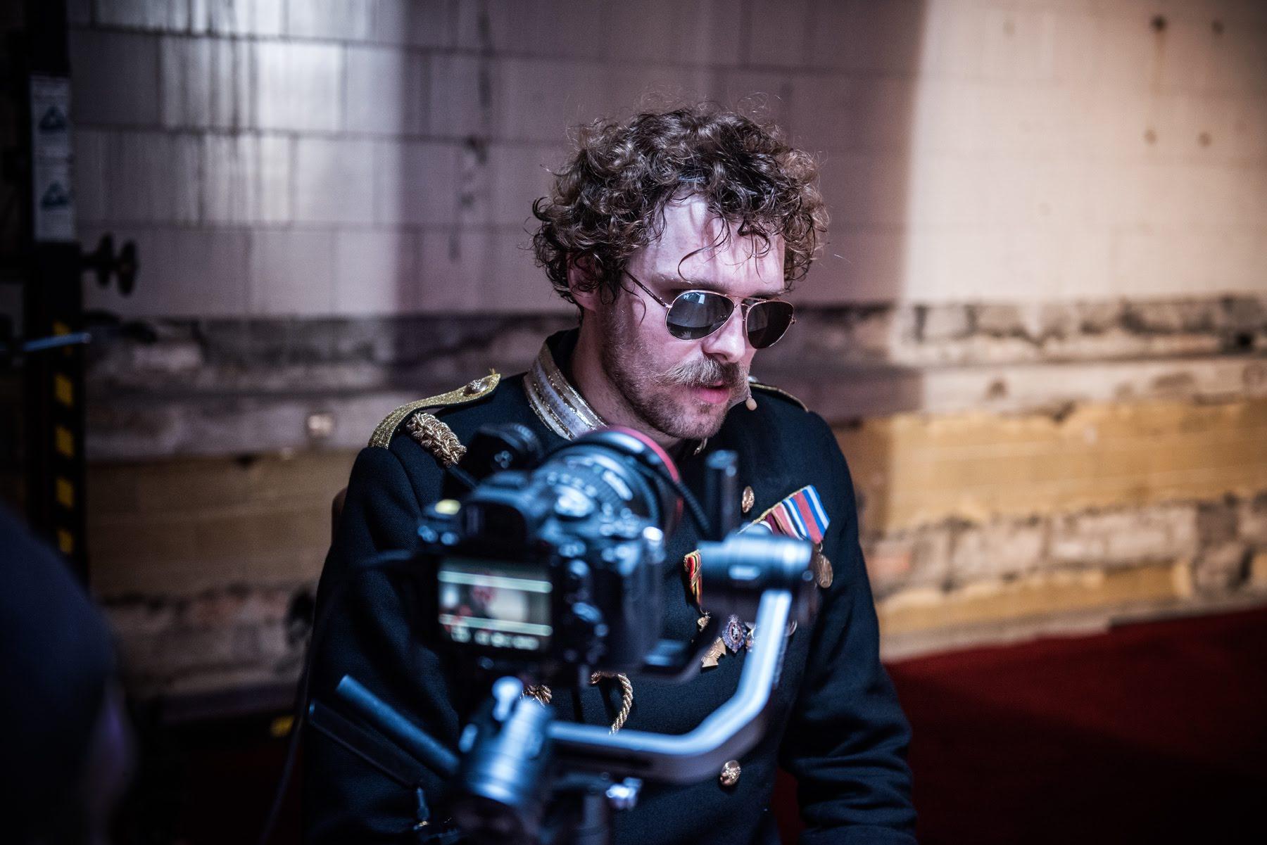 Aktor ubrany w mundur z okularami przeciwsłonecznymi na twarzy na tle kamiennej ściany. Na drugim planie aparat fotograficzny.