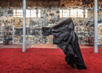 Tańcząca aktorka ubrana na czarno na kamiennej ścianie