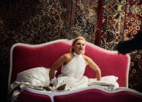 Aktora siedząca na łożu ubrana w biała sukienkę