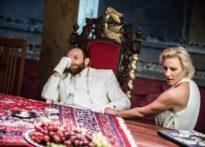 Zamyślony aktor siedzący na bogato zdobionym krześle oraz aktora siedząca przy stole