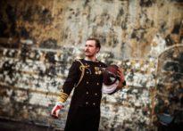 Aktor stojący pod kamienną ścianą , ubrany w mundur i trzymający w ręku szpadę i kask