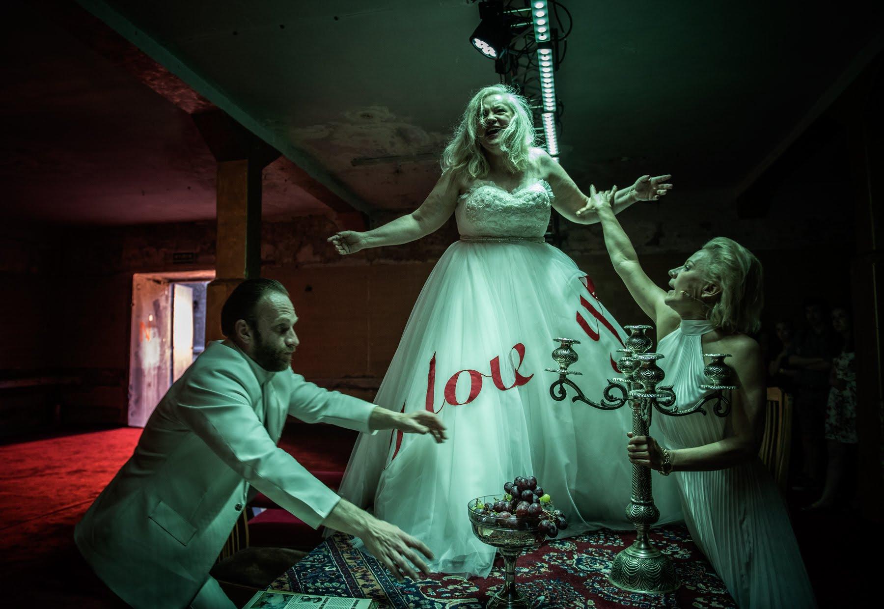 Aktorka ubrana w suknie ślubną chodząca po stole oraz dwoje aktorów asekurującą ją