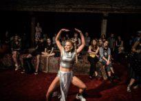 Na pierwszym planie tańcząca aktorka, na drugim publiczność