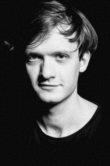 Czarno-biała fotografia. Mężczyzna z długą grzywką wpatruje się w obiektyw, lekko uśmiechnięty. Na zdjęciu: Michał Sikorski.