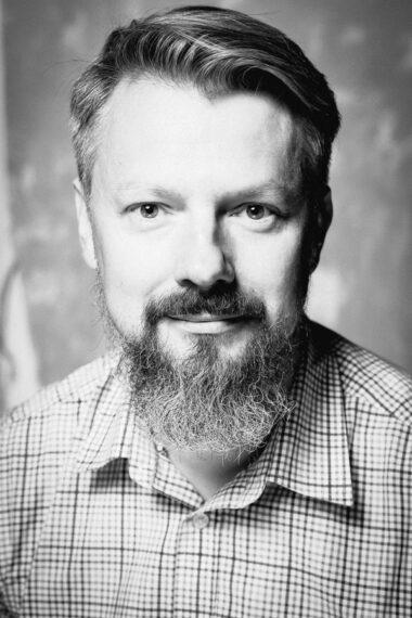 Czarno-biała fotografia. Mężczyzna w koszuli w kratę z wąsem i długą brodą. Na zdjęciu: dyrektor Marcin Kowalski.