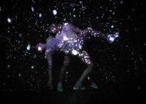 Dwóch aktorów na ciemnym tle w otoczeniu świateł przypominających rozgwieżdżone niebo.Na zdjęciu Monika Roszko i Konrad Cichoń
