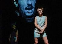 Na pirwszym planie stojąca aktorka, z tyłu druga stojąca aktorka, w tle wyświetlona głowa aktora. Na zdjęciu Monika Roszko, Barbara Krasińska oraz Konrad Cichoń