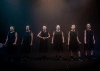 Sześć kobiet ubranych w czarne sukienki na czarnym tle.