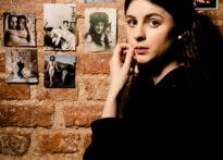 Kobieta o długich ciemnych włosach ubrana na czarno opiera się bokiem o ceglaną ścianę, na której wiszą zdjęcia. Jej ręce są skrzyżowane, jedna z dłoni przy twarzy. Na zdjęciu Aleksandra Samelczuk.