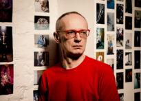 Mężczyzna w czerwonym swetrze i okularach z czerwonymi oprawkami opiera się o ścianę, na której wiszą zdjęcia. Na zdjęciu Andrzej Szubski.